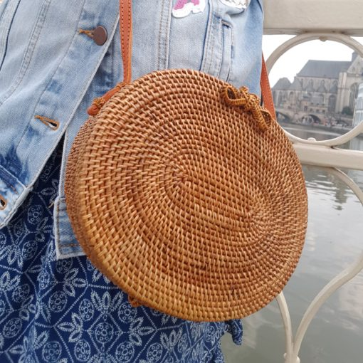 ovale rattan sling bag on bridge