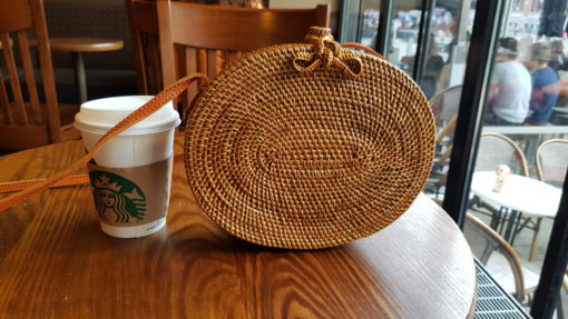 ovale atta sling bag on table with starbucks cup