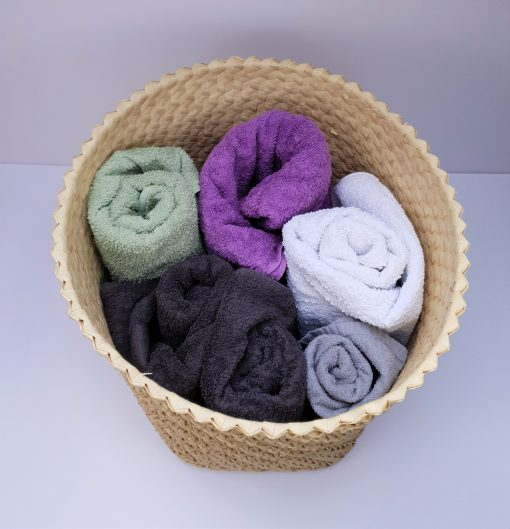 natural basket with folded towels inside from above